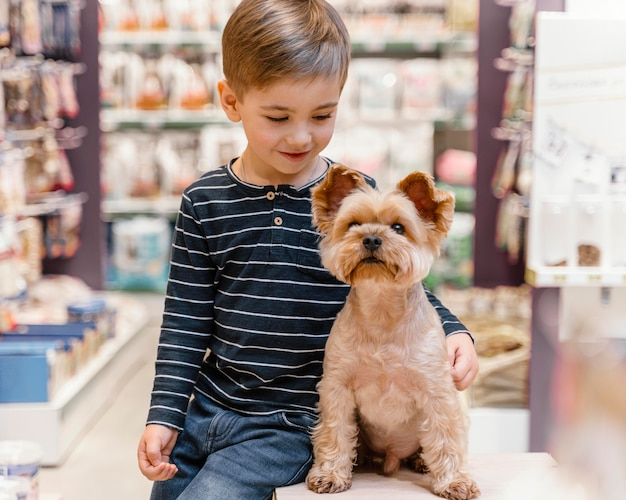 Simpatico cagnolino al negozio di animali con il proprietario Foto Gratuite