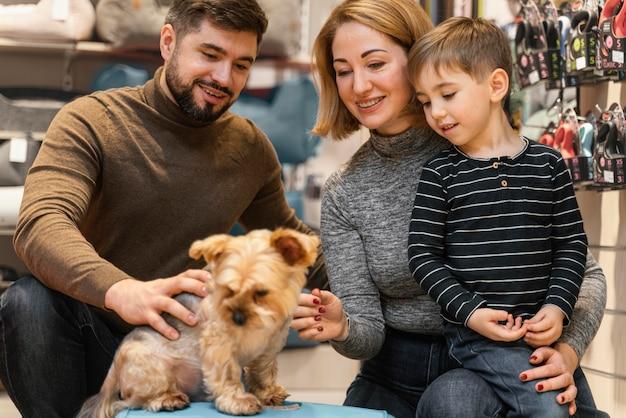 Piccolo cane sveglio con i proprietari al negozio di animali Foto Gratuite