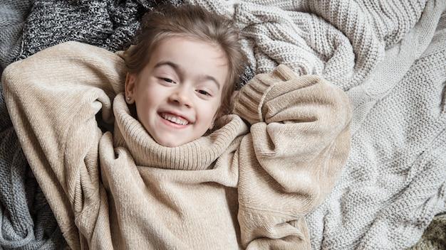 ニットセーターのかわいい小さな楽しい女の子 無料写真