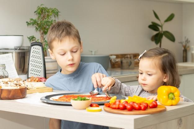귀여운 소녀 2-4 회색 드레스와 소년 7-10 티셔츠 요리 피자 함께 부엌에서. 형제와 자매 요리 프리미엄 사진