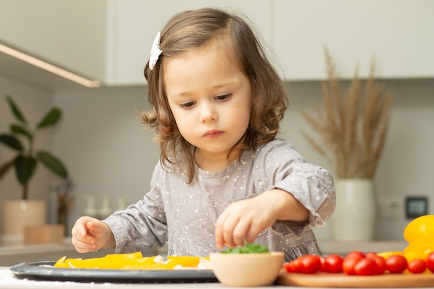 부엌에서 피자를 요리하는 회색 드레스에 귀여운 소녀 2-4. 아이가 피자베이스에 재료를 준비 프리미엄 사진