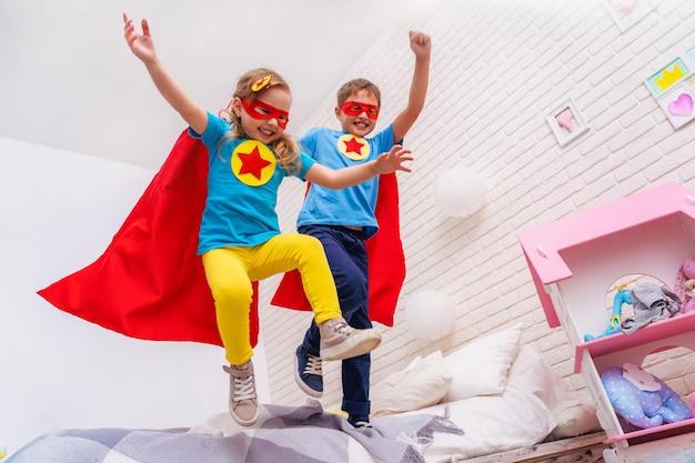 Симпатичная маленькая девочка и мальчик прыгают с кровати, чтобы летать, играть в супергероя Premium Фотографии