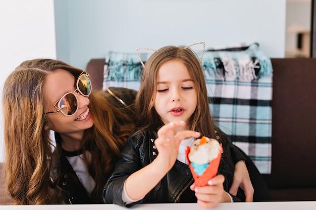 Милая маленькая девочка и ее привлекательная жизнерадостная мама в модных солнцезащитных очках веселятся дома и едят десерт. Бесплатные Фотографии