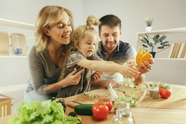 かわいい女の子と彼女の美しい両親は、自宅のキッチンでサラダを作りながら野菜を切って笑っています。家族のライフスタイルの概念 無料写真
