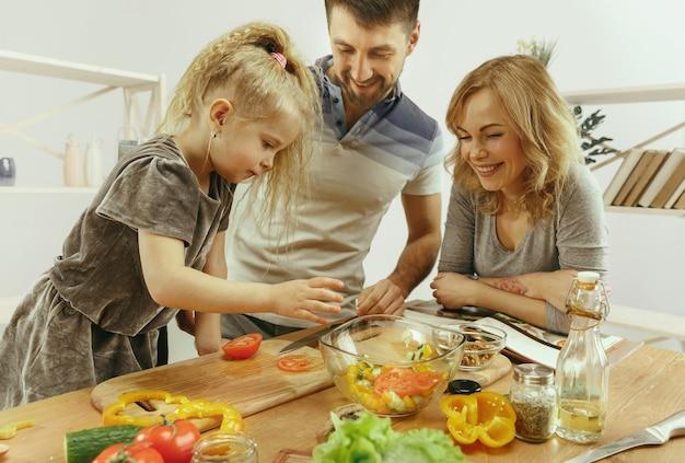かわいい女の子と彼女の美しい両親は自宅のキッチンで野菜を切っています 無料写真