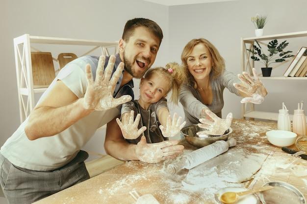 귀여운 어린 소녀와 집에서 부엌에서 케이크 반죽을 준비하는 그녀의 아름다운 부모. 가족 라이프 스타일 개념 무료 사진