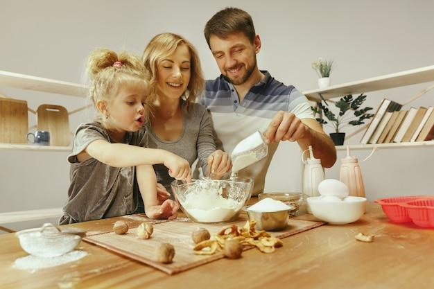 かわいい女の子と彼女の美しい両親は、自宅のキッチンでケーキの生地を準備しています 無料写真