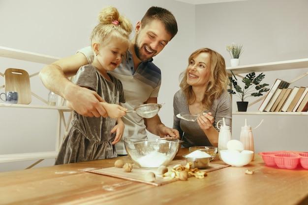 귀여운 어린 소녀와 집에서 부엌에서 케이크 반죽을 준비하는 그녀의 아름다운 부모. 무료 사진