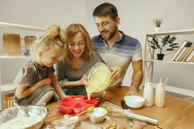 Милая маленькая девочка и ее красивые родители готовят тесто для торта на кухне дома. Бесплатные Фотографии