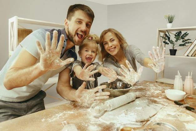 Милая маленькая девочка и ее красивые родители готовят тесто для торта на кухне дома Бесплатные Фотографии