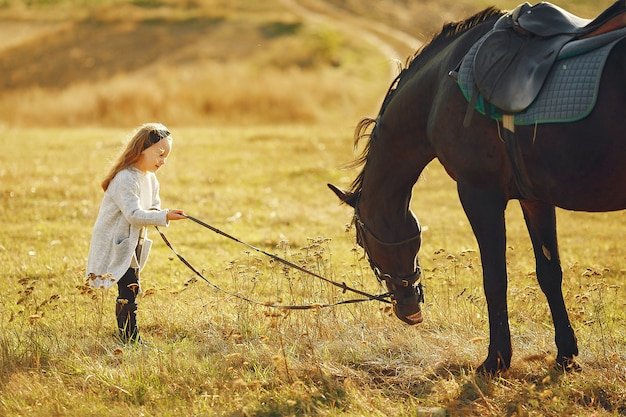 Cute little girl in a autumn field with horse Free Photo