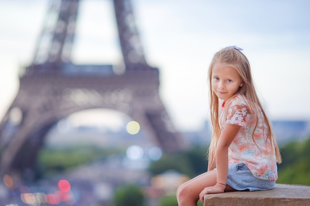 Cute little girl background the eiffel tower during summer vacation in paris Premium Photo
