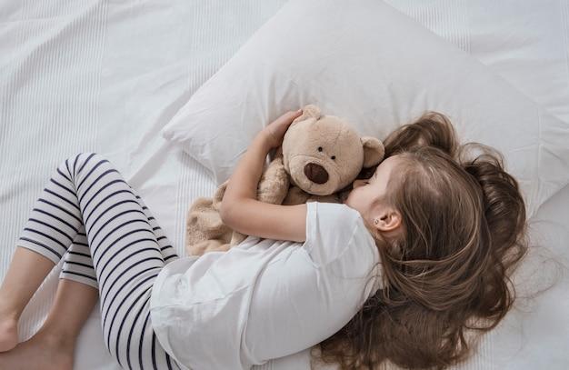 Bambina sveglia a letto con peluche. Foto Gratuite
