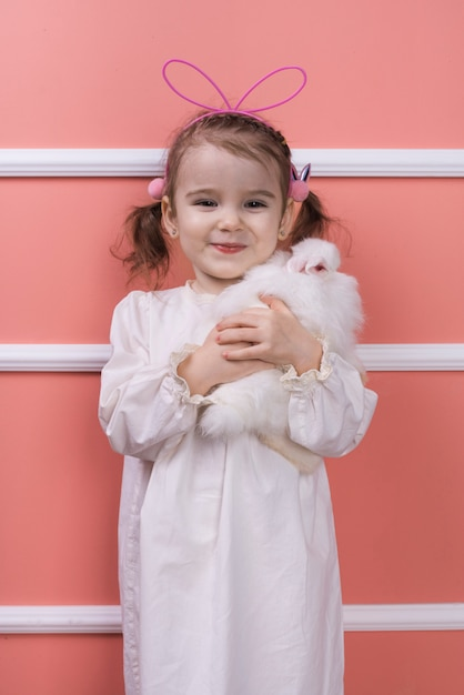 Cute little girl in bunny ears with rabbit Free Photo