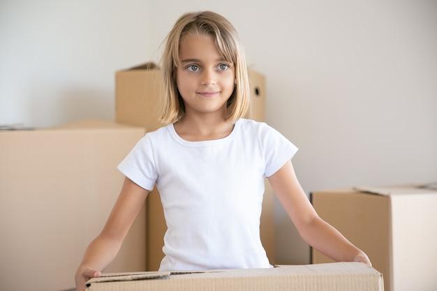 Милая маленькая девочка, несущая картонную коробку и глядя в сторону Бесплатные Фотографии