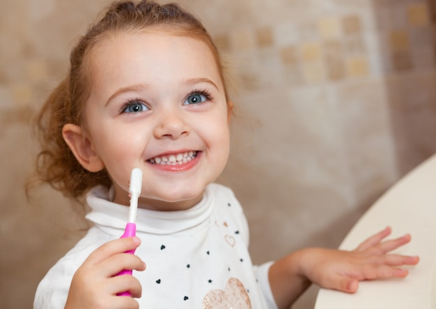 Cute little girl cleaning tooth with brush. Premium Photo