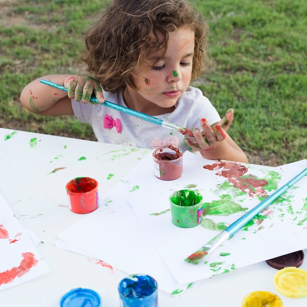 Cute little girl drawing painting on canvas in park Free Photo