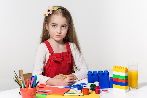 Cute little girl drawing with paint and paintbrush at home Free Photo