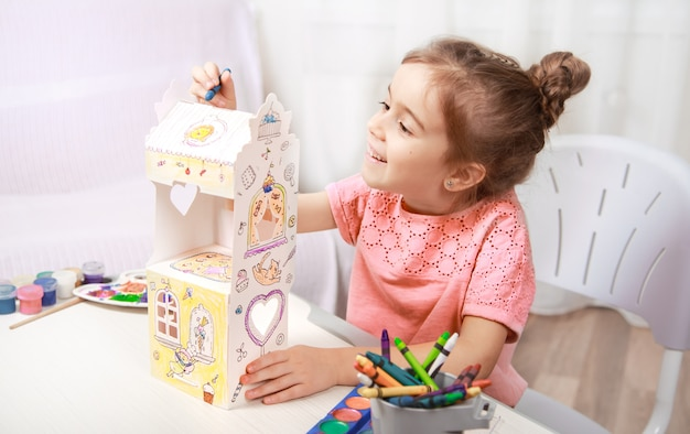 Cute little girl drawing with pencils at home Free Photo