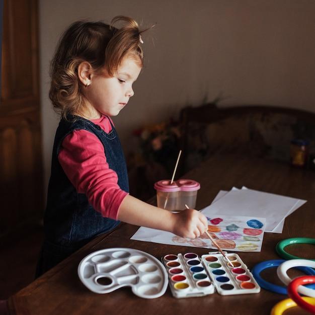 La bambina sveglia disegna un cerchio di vernici colorate Foto Gratuite