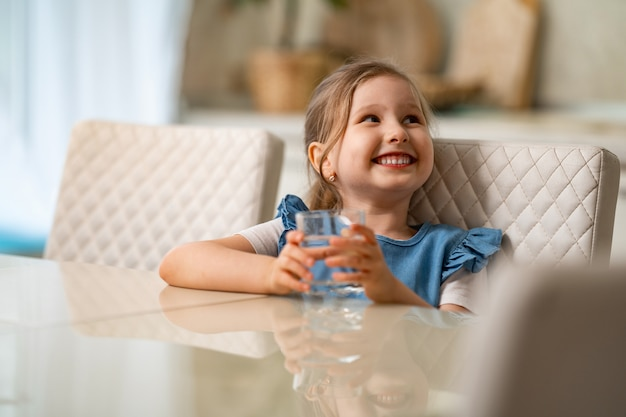 Cute little girl drinking water in kitchen at home. prevention of dehydration Premium Photo
