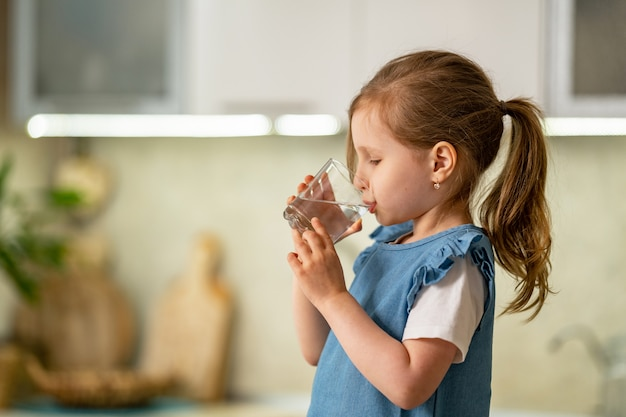 Cute little girl drinking water in kitchen at home. water balance. Premium Photo