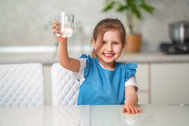 Cute little girl drinking water in kitchen at home Premium Photo