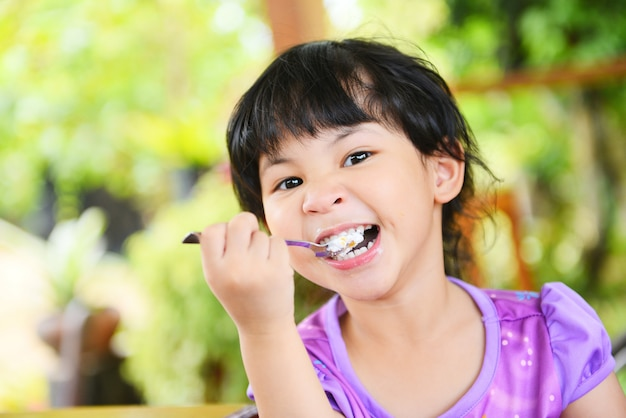 Cute little girl eating cake. asian child happy and holding a spoon into the mouth with cake on dining table , selective focus Premium Photo