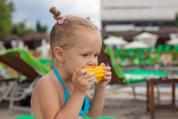 Cute little girl eating corn at the pool on vacation Premium Photo