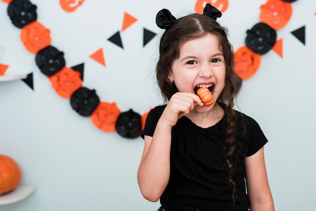 Cute little girl eating a pumpking candy Free Photo