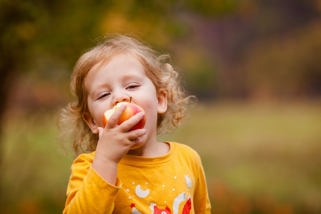 Cute little girl eating red delicious apple Premium Photo