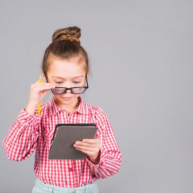 Cute little girl in glasses using tablet Free Photo
