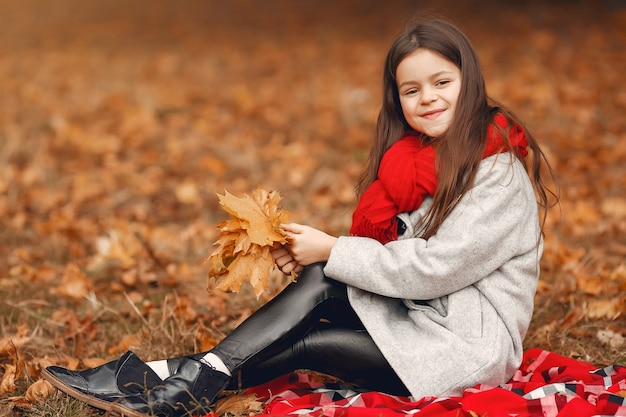 Cute little girl in a gray coat playing in a autumn park Free Photo