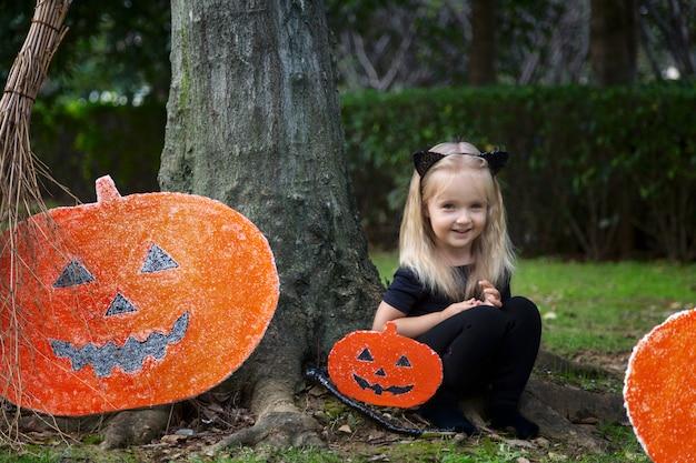 Cute little girl in halloween costume sitting near pumpkin decoration Premium Photo