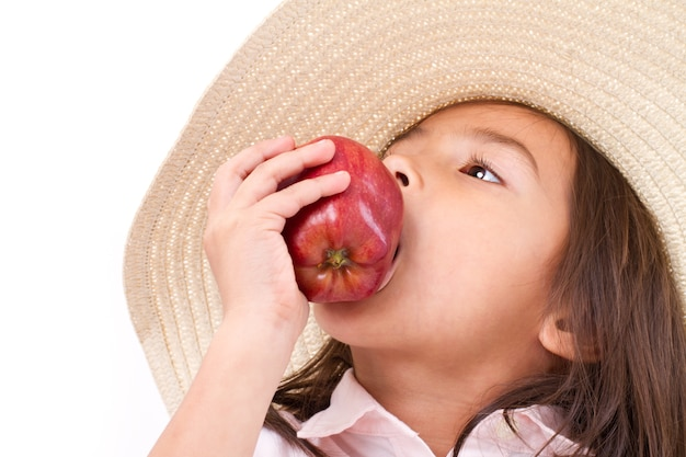 Cute little girl, hand holding, biting red apple Premium Photo