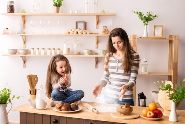 Cute little girl and her beautiful mother are sprinkling the dough with flour and smiling while baking Premium Photo