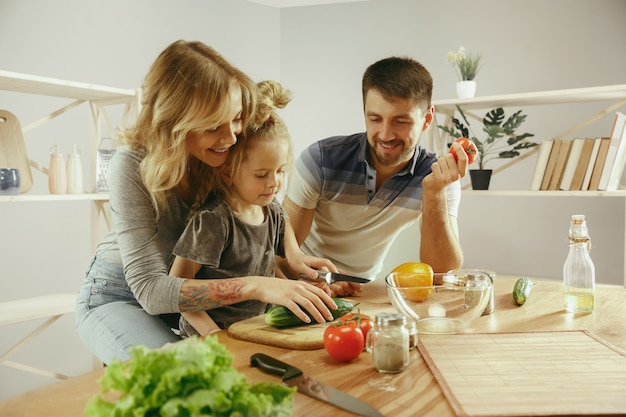 Cute little girl and her beautiful parents are cutting vegetables and smiling while making salad in kitchen at home. family lifestyle concept Free Photo