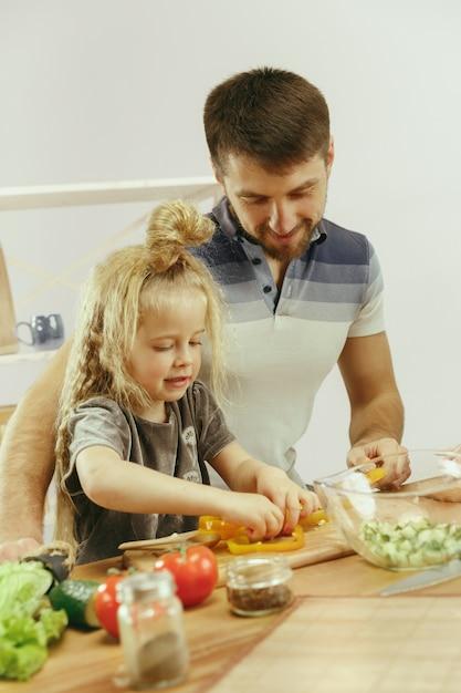 La bambina sveglia ei suoi bellissimi genitori stanno tagliando le verdure e sorridendo mentre fanno l'insalata in cucina a casa Foto Gratuite