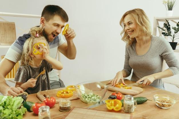 La bambina sveglia ei suoi bellissimi genitori stanno tagliando le verdure e sorridendo mentre fanno l'insalata Foto Gratuite