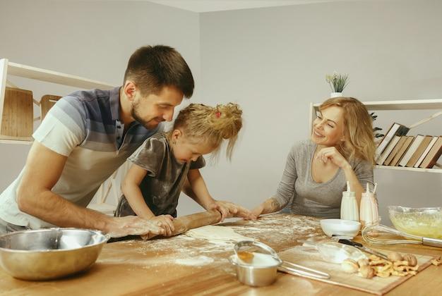 Bambina sveglia ed i suoi bei genitori che preparano la pasta per la torta in cucina a casa Foto Gratuite