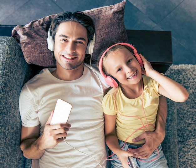 Cute little girl and her handsome father in headphones. Premium Photo
