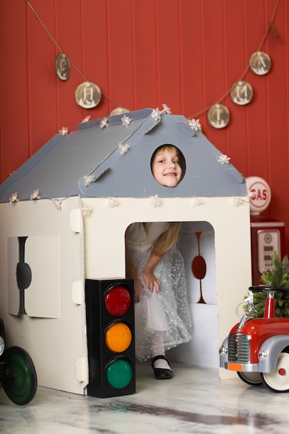 Cute little girl hiding in a cardboard house and playing with a big toy fire engine. happy childhood. Premium Photo