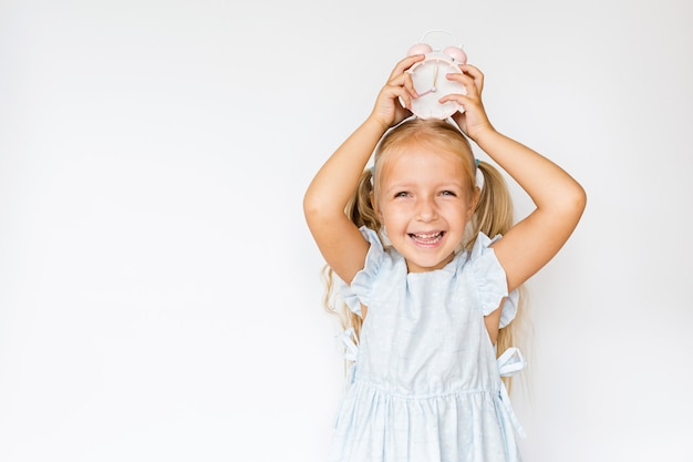 Cute little girl holding alarm clock on white  with copyspace Premium Photo