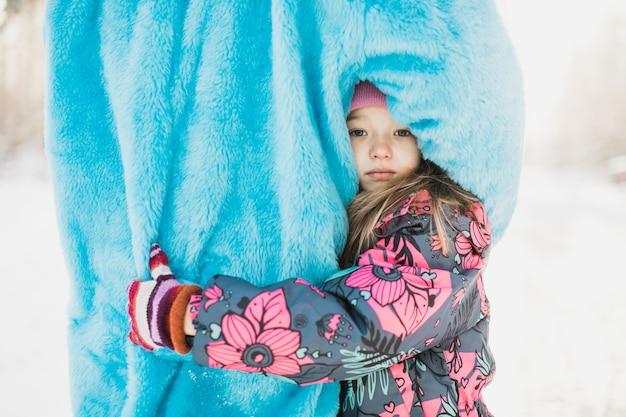 ふわふわの青い衣装で人を抱き締めるかわいい女の子 無料写真