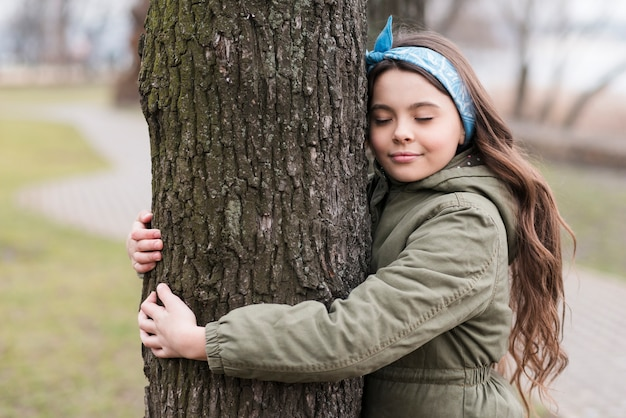 Cute little girl hugging a tree Free Photo