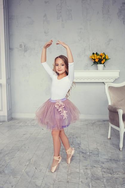 A cute little girl is dancing like a ballerina Premium Photo