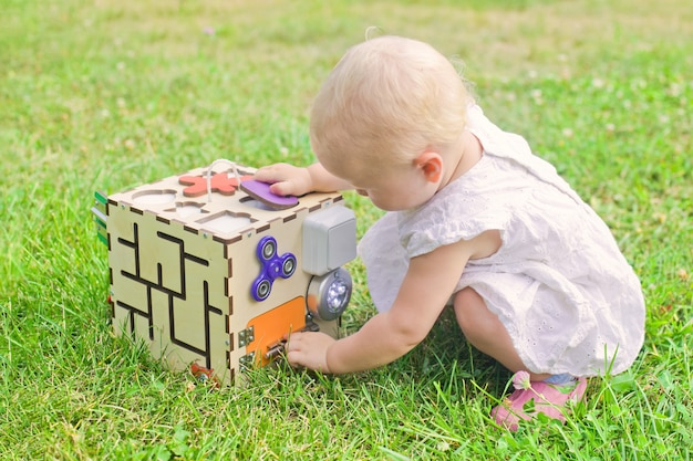 Cute little girl is playing with busiboard outdoors on green grass. educational toy for toddlers. girl opened door to cube of board. Premium Photo