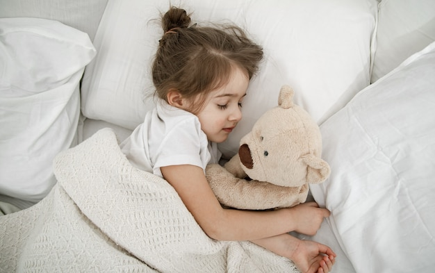A cute little girl is sleeping in a bed with a teddy bear toy . concept of child development and sleep. the view from the top. Free Photo