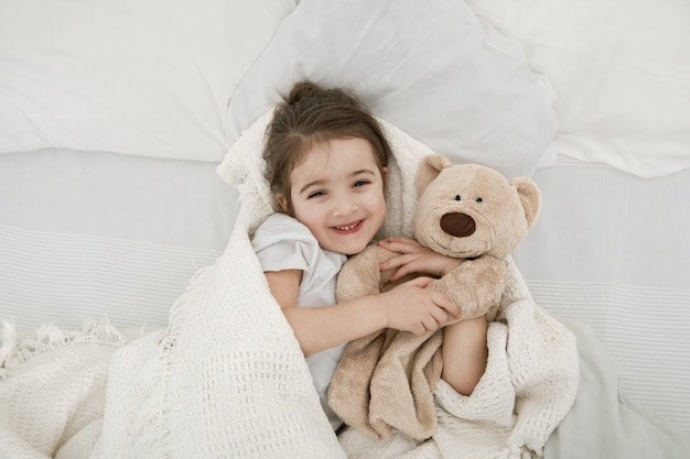 A cute little girl is sleeping in a bed with a teddy bear toy . Free Photo