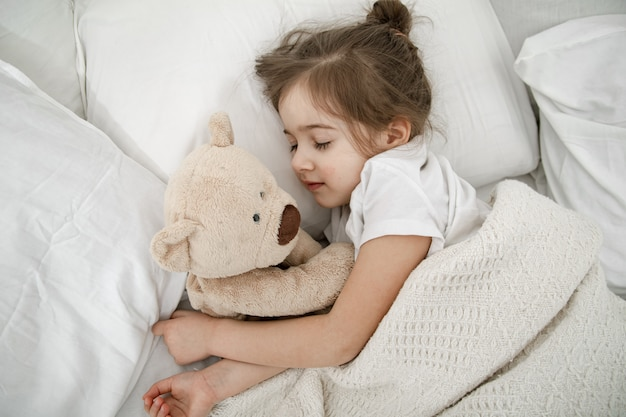 A cute little girl is sleeping in a bed with a teddy bear toy. Free Photo